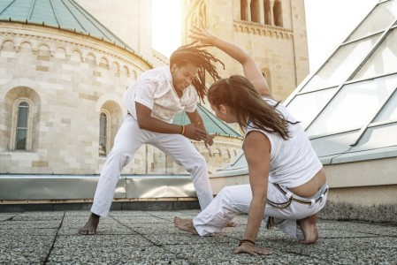 Young pair capoeira partners performing kicks outdoor